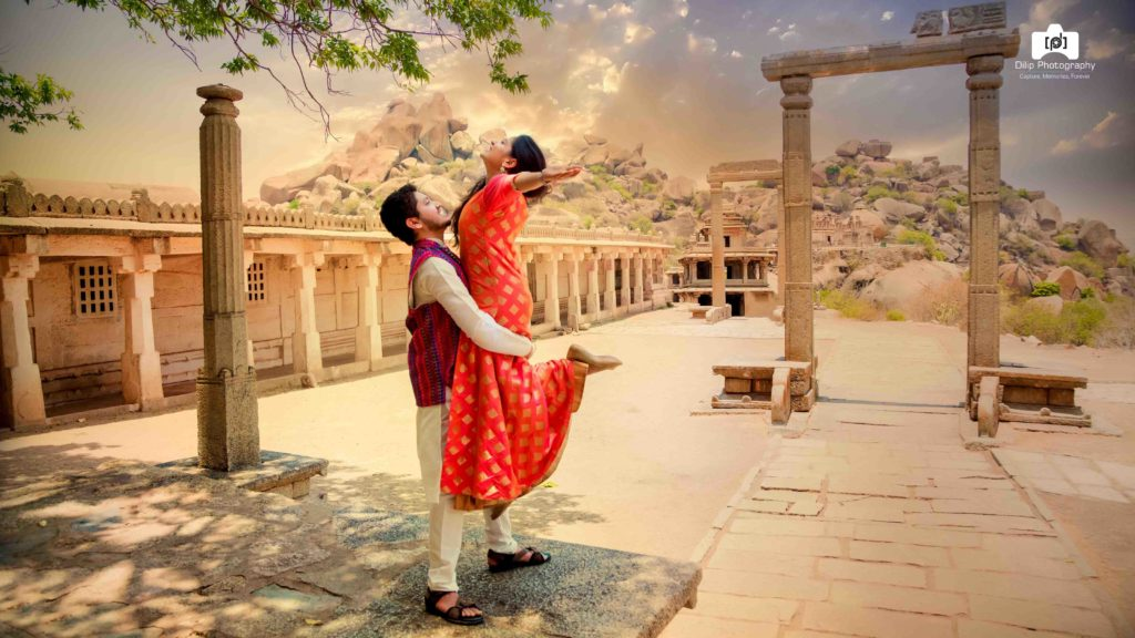candid pre wedding picture of groom lifting the bride in a temple
