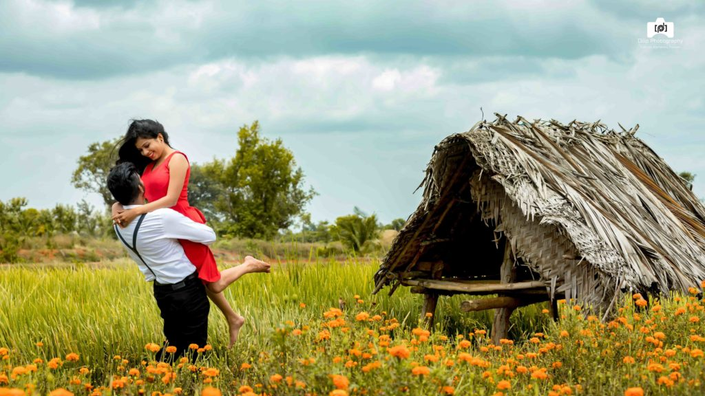 candid pre wedding picture of groom in formals picking up the bride in red skirt in a flower field