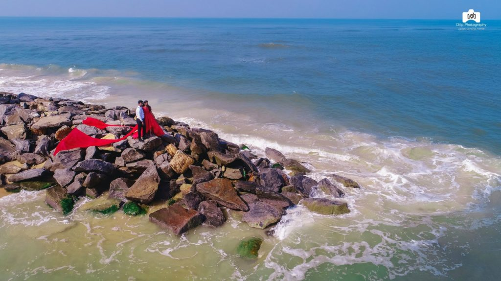 candid pre wedding drone picture of bride and groom standing on rocks and staring at the bright blue ocean