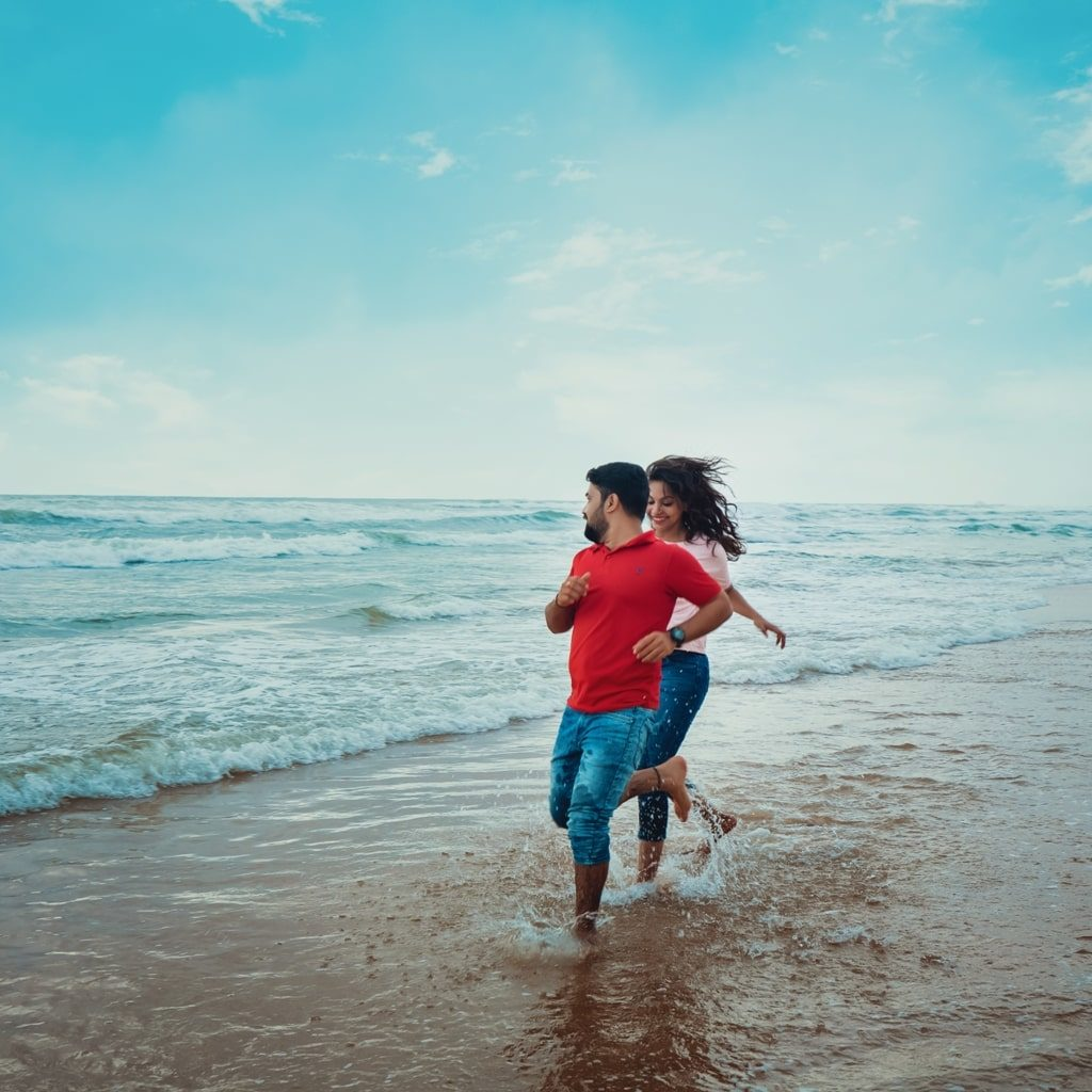 candid pre wedding picture of bride and groom running in the beach water