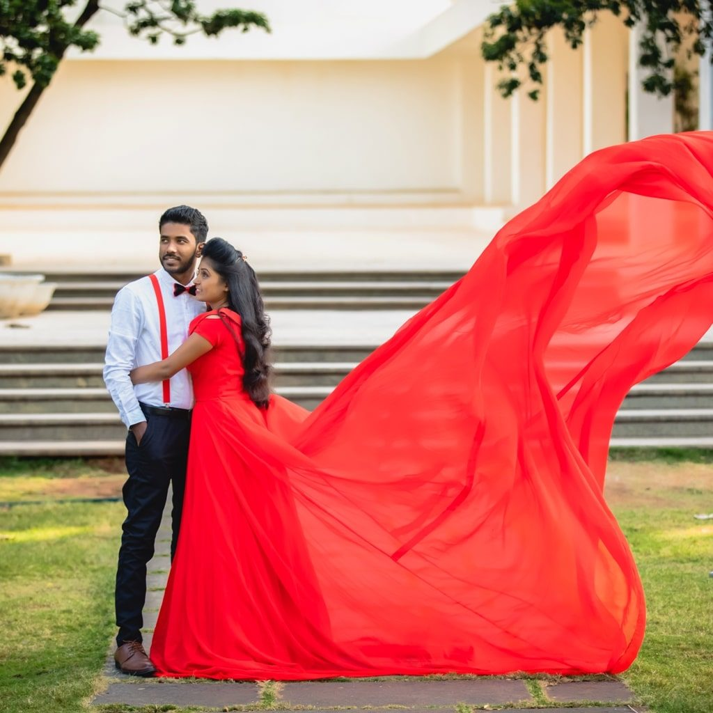 candid picture of bride with red dress in air hugging the groom