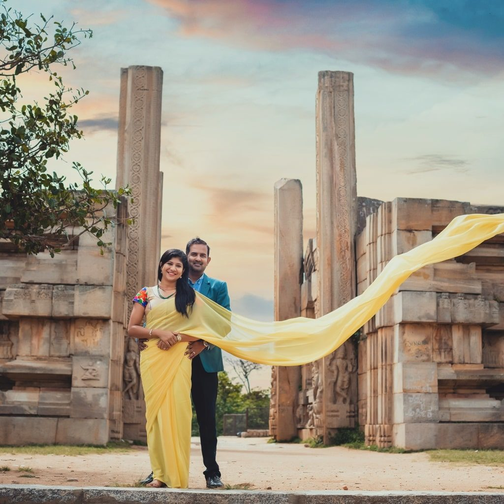pre wedding picture of groom holding bride's waist and bride's pallu flying