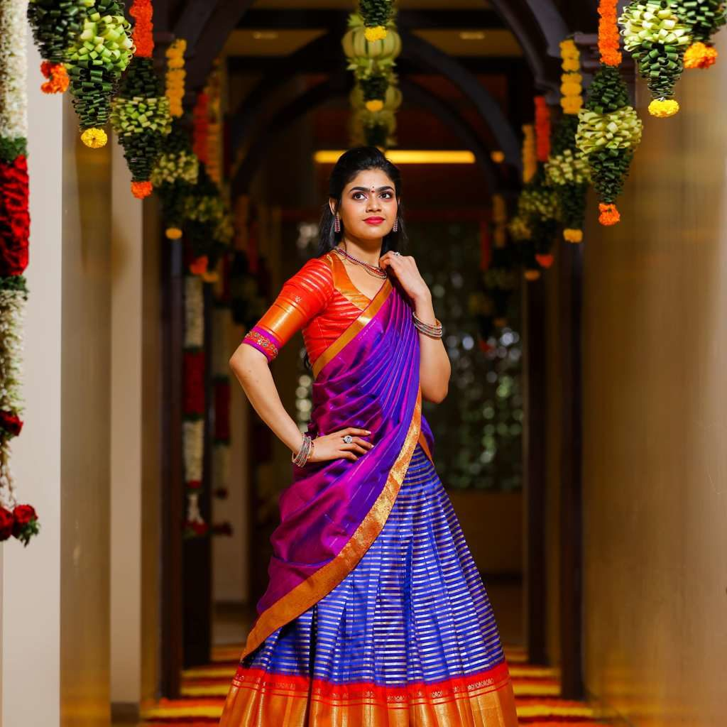 candid picture of sriramulu's daughter in a purple saree in a hallway with flower decorations
