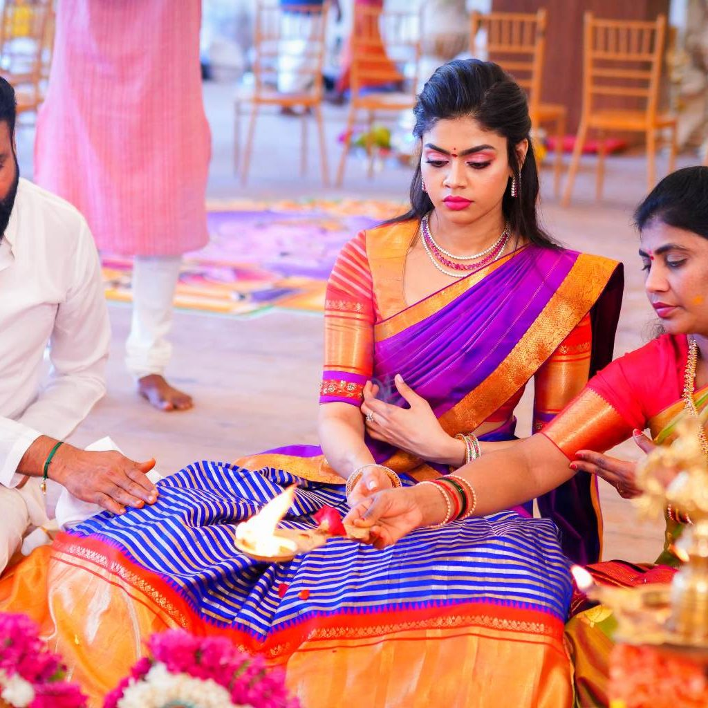 candid picture of sriramulu with wife and bride daughter performing aarati to god